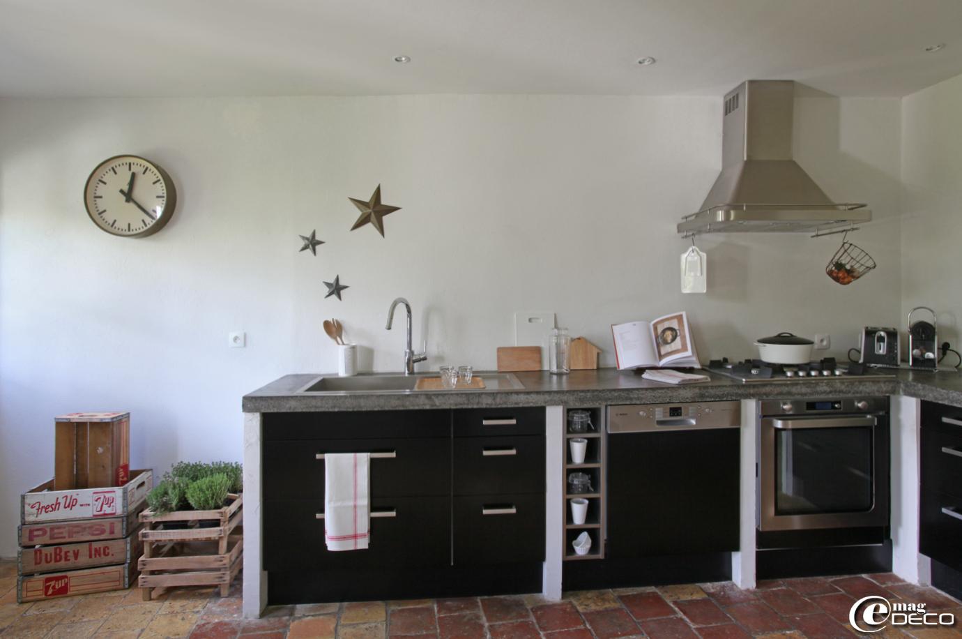Cuisine et hotte 'Ikea' avec un plan de travail en béton ciré, clayettes en bois empilées servant à présenter des herbes aromatiques