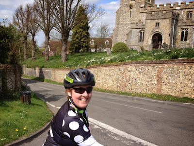 female cyclist near flint-built church