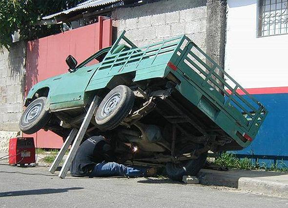 Hombre arreglando camioneta con tablas de madera