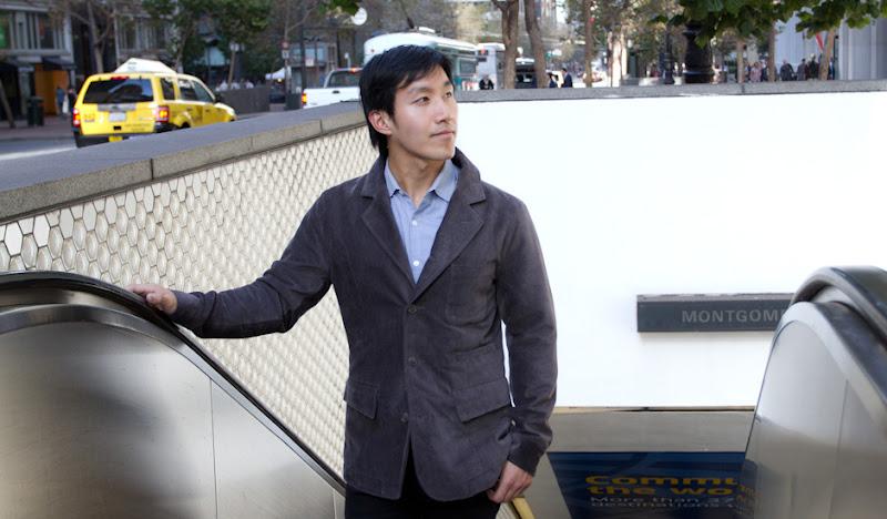 Chris rides escalator in Gray Reversible Drinking Jacket