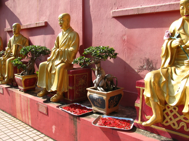 peppers drying at the feet of the statues