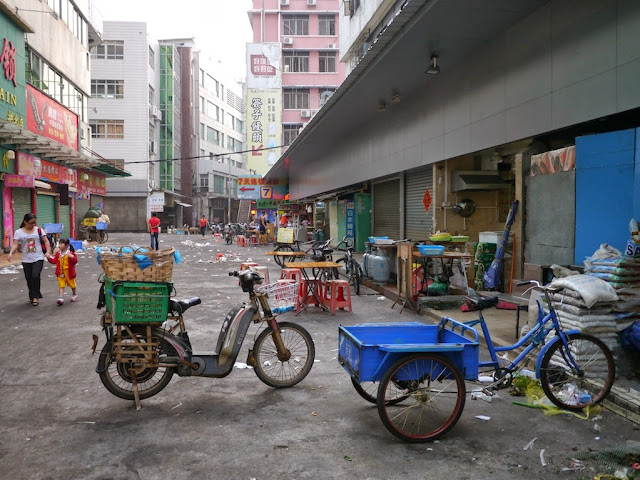 tricycle cart, electric bicycle, and woman walking with a little girl