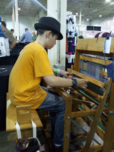 Joram sits at the loom and takes it all in