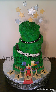 Mad hatter topsy turvy birthday cake with grass, Hollywood sign, stars, red carpet, palm trees, winding road and city skyline with edible stars topper
