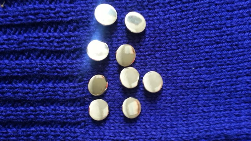 Nine bright silver disk buttons on a background of blue-violet handknit fabric
