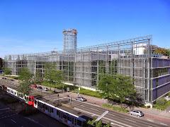 Gebäudekomplex, im Vordergrund Straßenbahn.