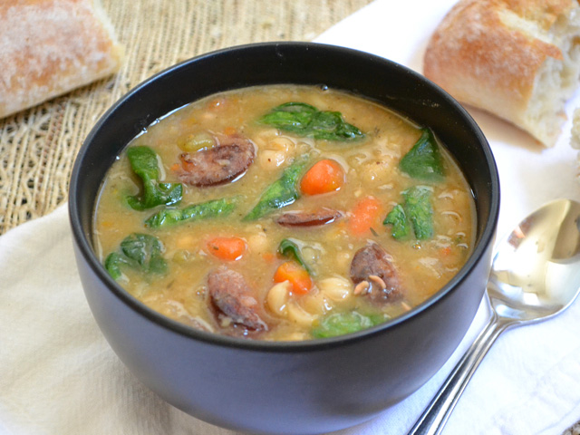 Navy Bean Soup with Sausage and Spinach in a black bowl with pieces of bread on the side