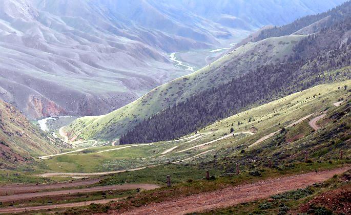 Blick von der Passhöhe Terskei-Torpok (3132 m, Тескей-Торпок, Тридцать три Попугаи, Tridzat Tri Popugai, 33 попугая) auf die 33 Serpentinen, die zum Wasserfall und Song-Köl hinabführen