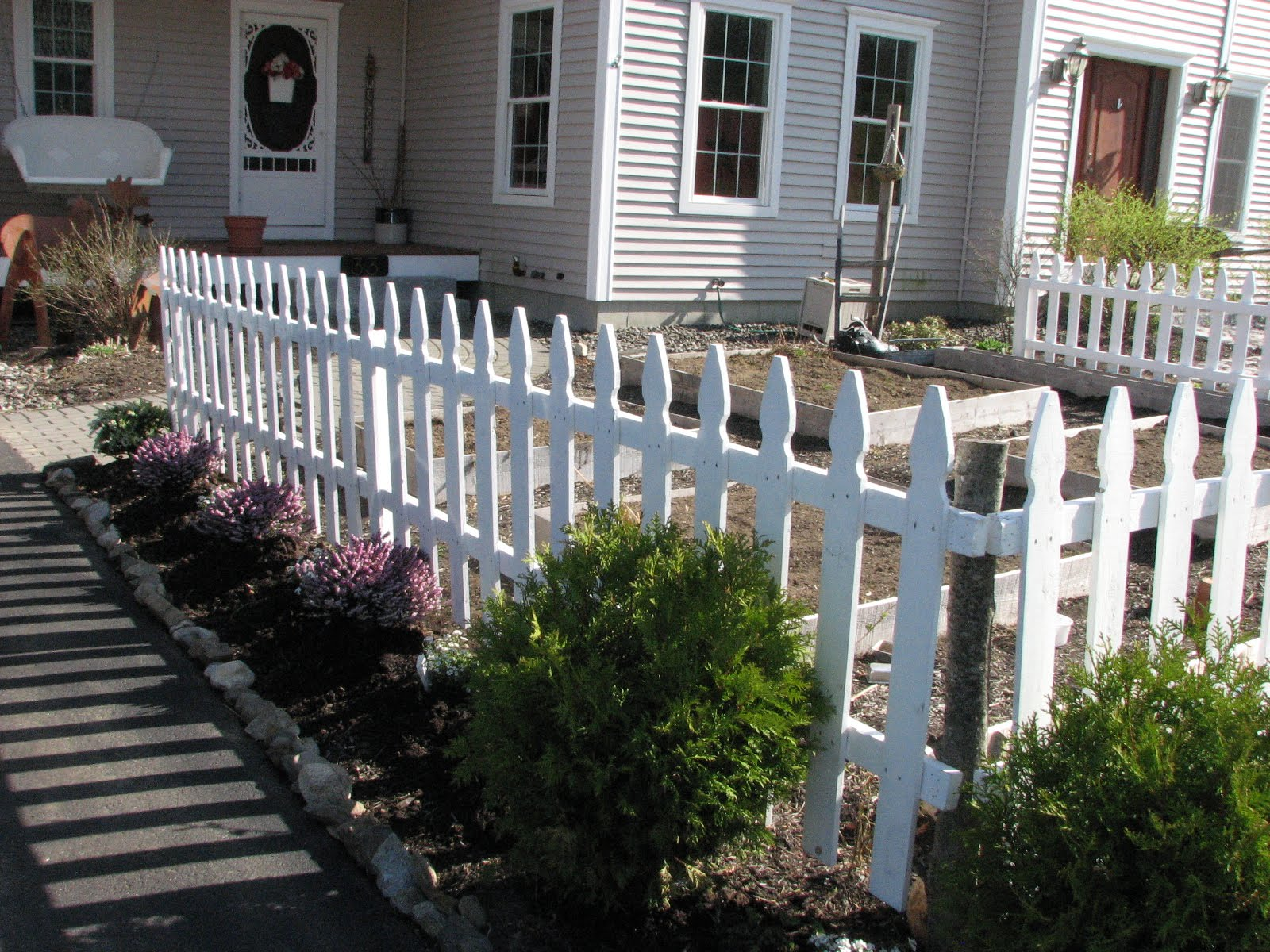two men and a little farm on the fence a white picket fence