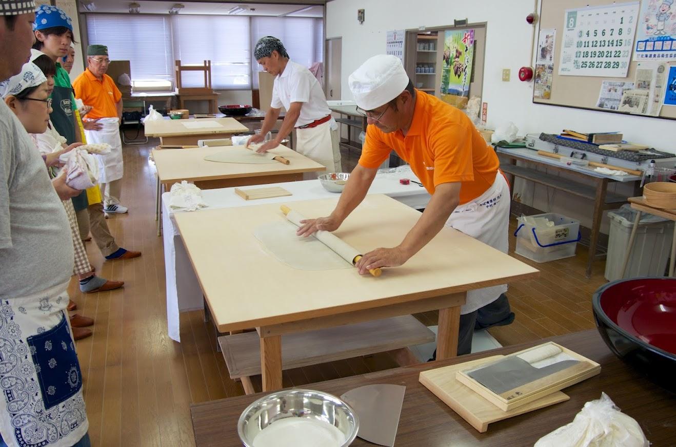 麺棒に生地を巻き、延し板にこするように引いて転がします