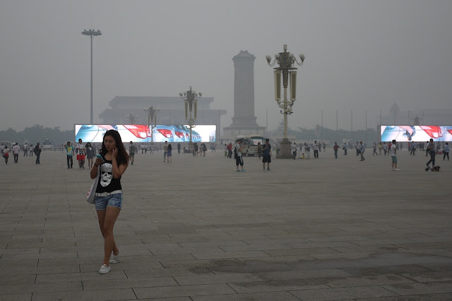 young woman walking and checking her phone at Tiananmen Square