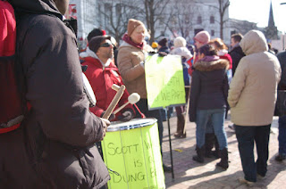 More protesters milling around. In the foreground, one is handling a green drum on which the words 'Scott,' 'is' and 'dung' are visible, the rest obscured by the glare of sunlight.