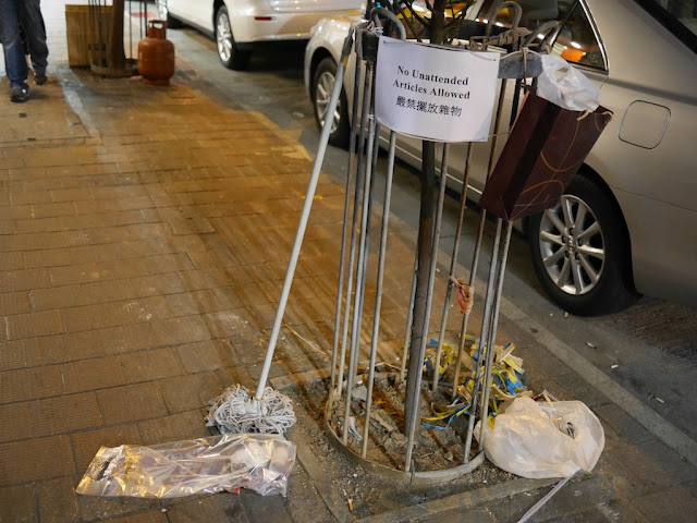 mop next to sign reading 'no unattended articles allowed' in Hong Kong
