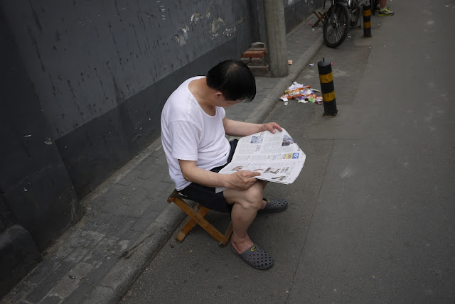 man reading a newspaper while sitting on a stool