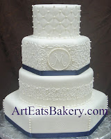 Four tier round and hexagon white fondant custom unique wedding cake with diamond quilt, curlicue royal icing, monogram, sugar pearls and blue ribbons design