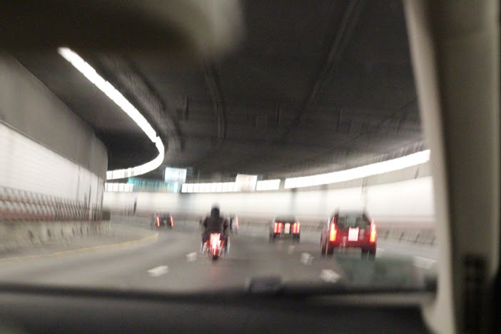 blurry picture of cars and a motorcycle in a curving tunnel