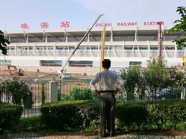Man looking at the new Zhuhai Railway Station from Sun Yat Sen Park in Macau