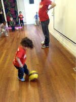 Toddler kicking a yellow football indoors