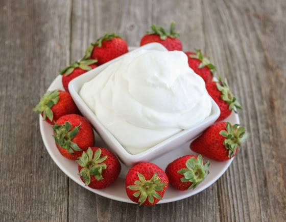 overhead photo of a bowl of coconut whipped cream surrounded by strawberries
