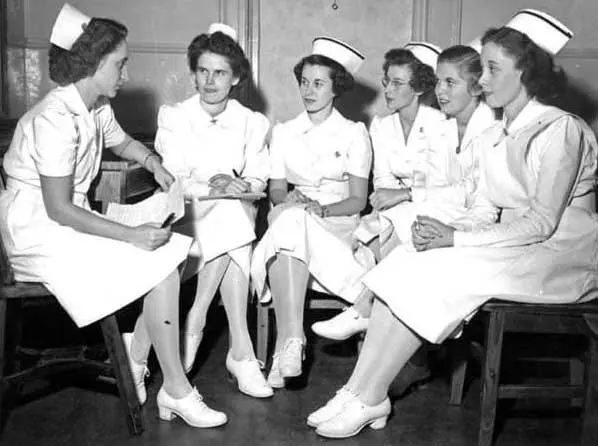 Six nurses sitting with each other while wearing old uniforms in ancient times