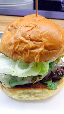 Tilt handcrafted burger of Carne Jefe with fresh ground, 100% natural, local chuck patty, topped of jalapenos, sliced avocado, cilantro, lettuce, tomato, thin-shaved onions, monterey cheese, mayo, and fresh squeezed lime on their house recipe bun