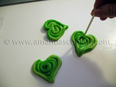 A photo of three green cookie dough spirals being shaped into a heart.