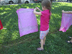 Children hang wet bandanas on a fence to dry.