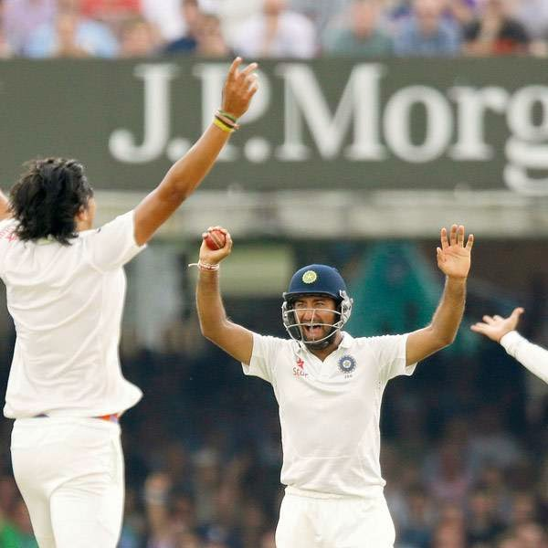 India's Cheteshwar Pujara, center, celebrates catching out England's Moeen Ali off an Ishant Sharma, left, delivery on the fifth day of the second cricket test match between England and India at Lord's cricket ground in London, Monday, July 21, 2014.