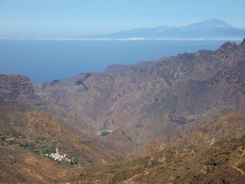Berglandschaft Gran Canarias, mit einem kleinen Dorf, einem Stausee und Teneriffa mit dem Teide im Hintergrund.