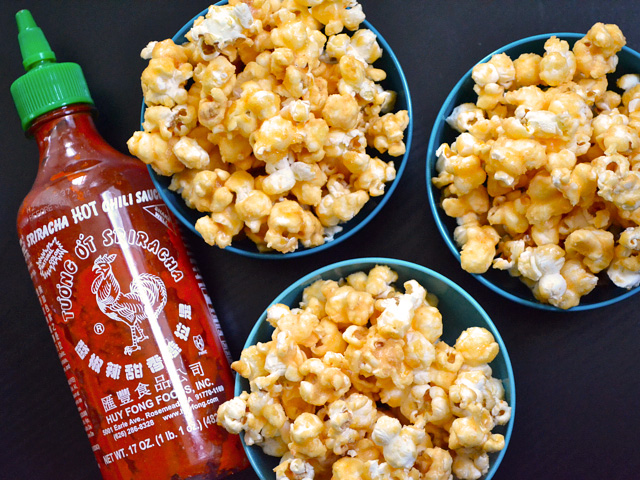 three small bowls of Sriracha Caramel Corn with a bottle of sriracha on the side
