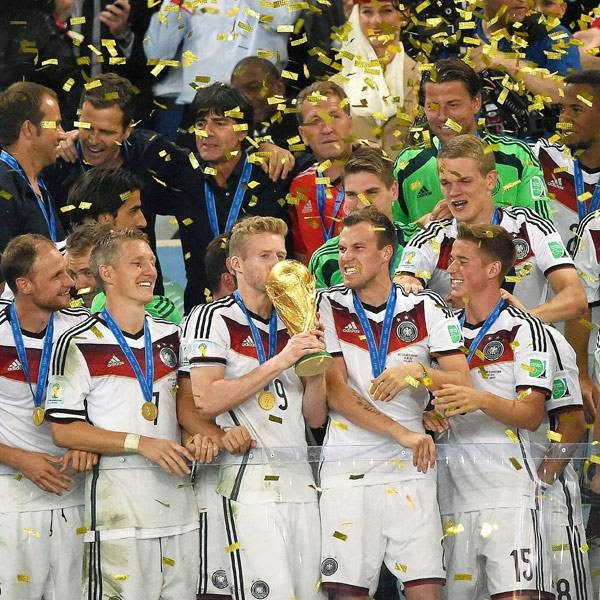 Germany's forward Andre Schuerrle (front C) and team-mates celebrate with the World Cup trophy after they won the 2014 FIFA World Cup final football match between Germany and Argentina 1-0 following extra-time at the Maracana Stadium in Rio de Janeiro, Brazil, on July 13, 2014.