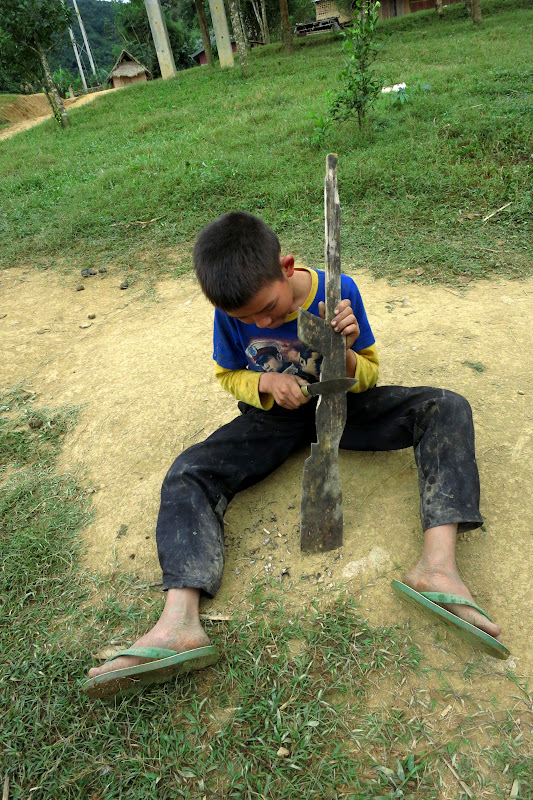Little boy using a large knife to carve a toy rifle