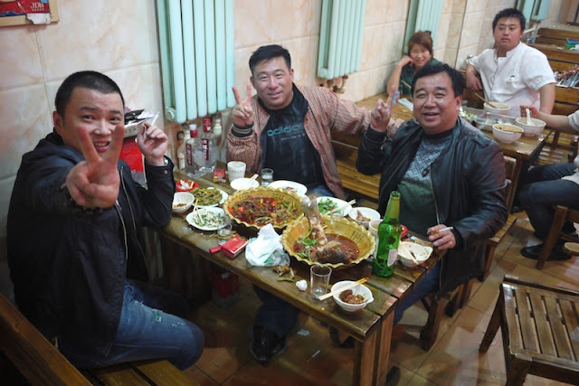 three men eating and drinking at a restaurant in Yinchuan, NIngxia