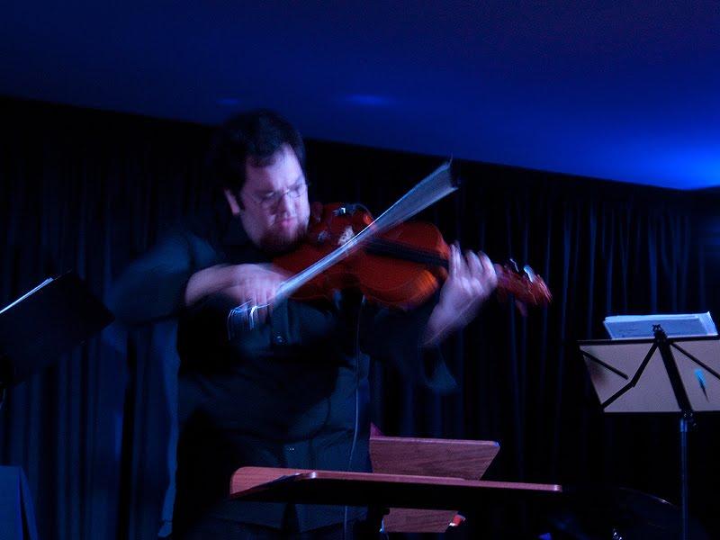 Fotografia mostrando o músico em acção, mostrando o movimento do arco