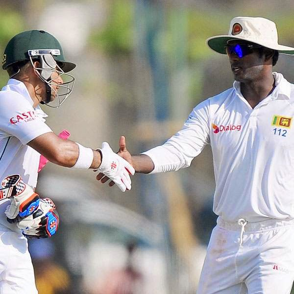 South Africa cricketer JP Duminy (L) is congratulated by Sri Lankan captain Angelo Mathews after scoring a century (100 runs) during the second day of the opening Test match between Sri Lanka and South Africa at the Galle International Cricket Stadium in Galle on July 17, 2014.