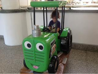 green tractor toy with toddler