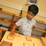 Preschool boy touching rough and smooth board material at private Montessori school in Huntington Beach.