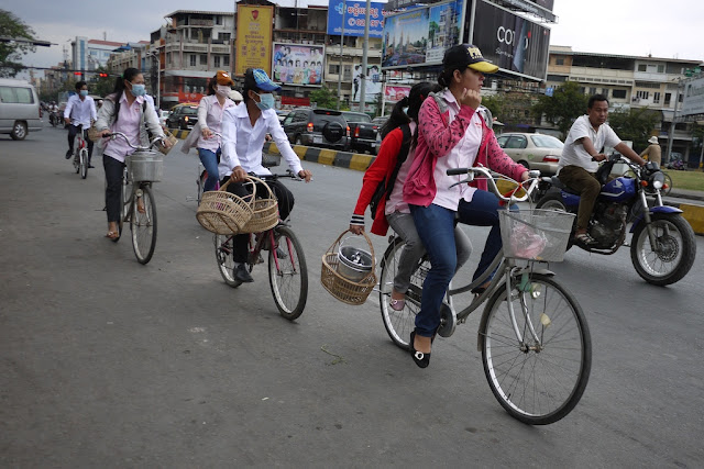 young women carrying baskets while riding bicycles