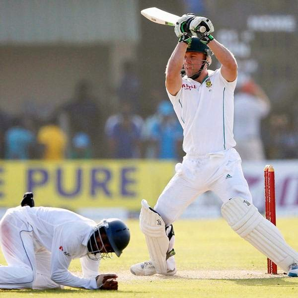 South Africa's AB de Villiers (C) plays a shot as Sri Lanka's Kaushal Silva (L) ducks from the ball next to Dinesh Chandimal during the first day of their first test cricket match in Galle July 16 2014.
