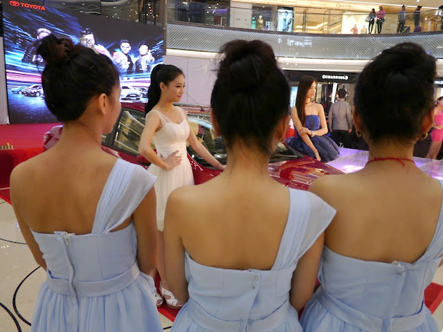 backs of three young women facing two other young women posing with a new car in a shopping mall in Changsha