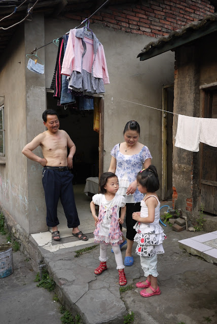 family of four standing outside their home