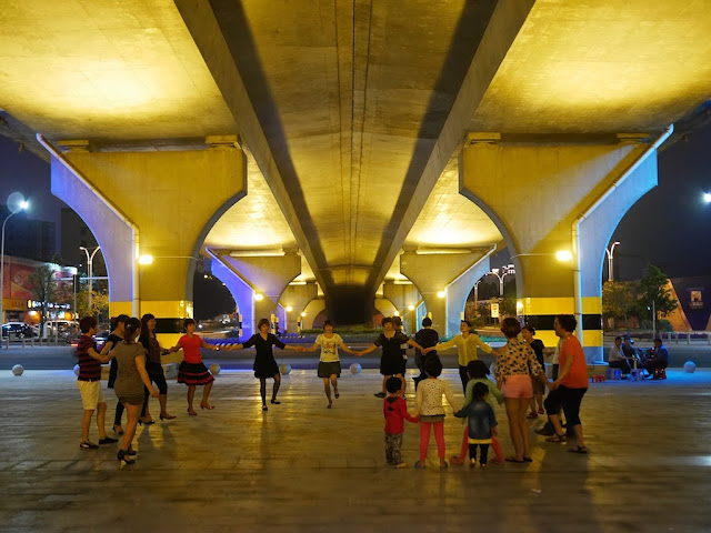 Adults and children holding hands in a circle as they dance underneath the Zhanjiang Bay Bridge.