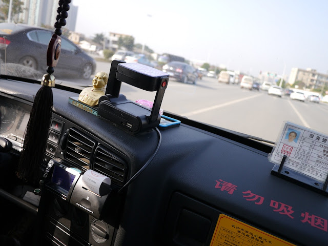 a bust of Mao Zedong on top a Changsha taxi dashboard