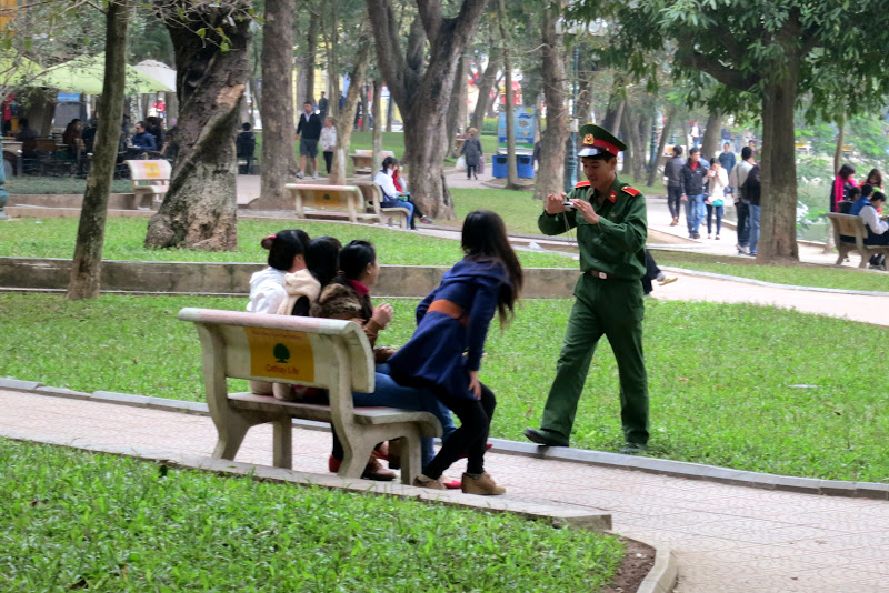 Police officer taking photos of friends at Hoàn Kiếm lake