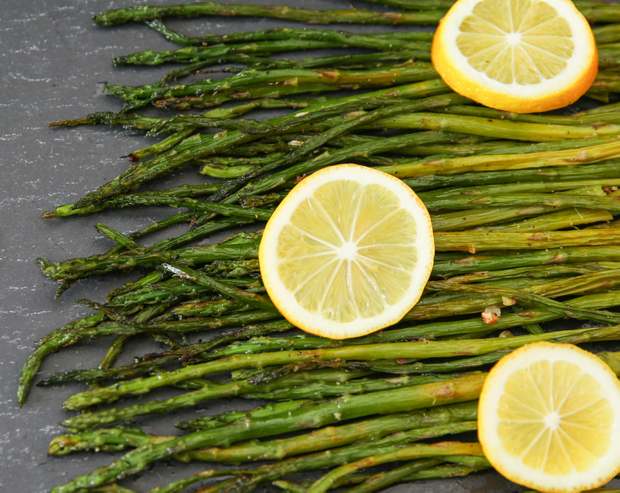 overhead photo of cooked asparagus with lemon slices