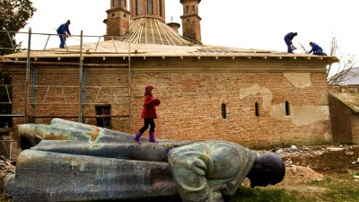 A church is restored, while a statue of Lenin is trampled underfoot