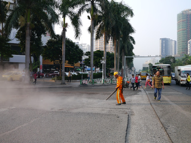 man using a blower to move gravel and creating a large dust cloud on a street in Zhuhai