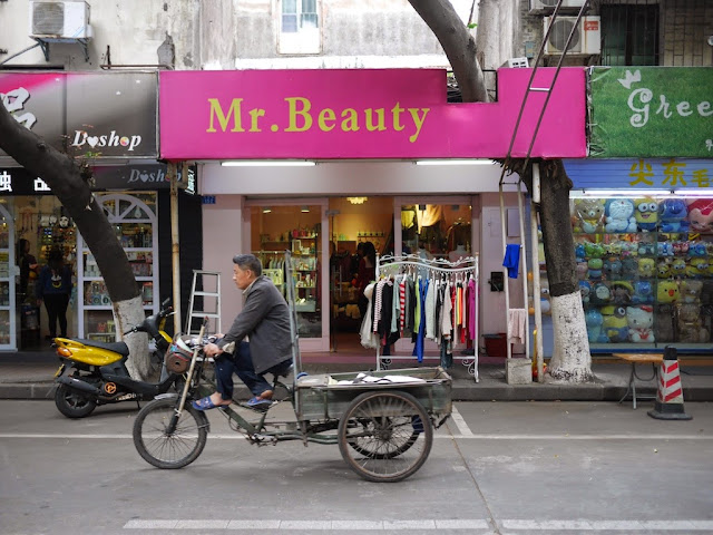 man riding a tricycle-cart past a store named Mr. Beauty