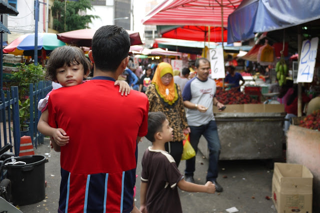 sleepy girl being carried at Bazaar Baru Chow Kit in Kuala Lumpur, Malaysia