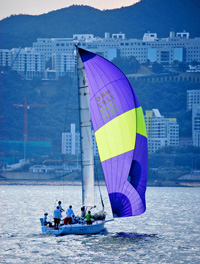 J/92 sailing downwind off Hong Kong waterfront in China